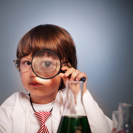 boy studying a substance in a test tube with a magnifying glass photo