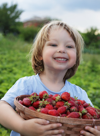 cheerful boy with  basket of berries photo