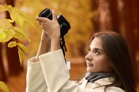 girl with camera in autumn forest photo
