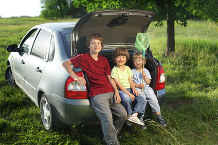 Three cheerful child sitting in the trunk of a car on nature photo