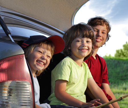 car trunk: Three cheerful child sitting in the trunk of a car on nature