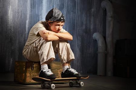 sad teenager: sad teenager sitting on skateboard Stock Photo