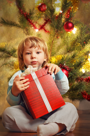 happy boy with christmas gift near Christmas tree photo