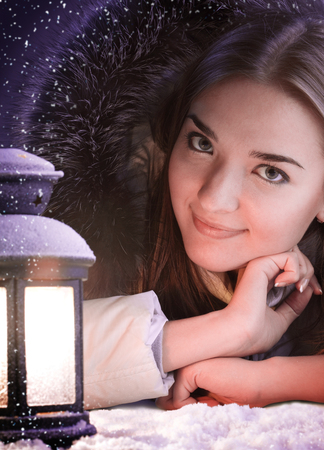 beautiful girl on winter snow with lantern photo