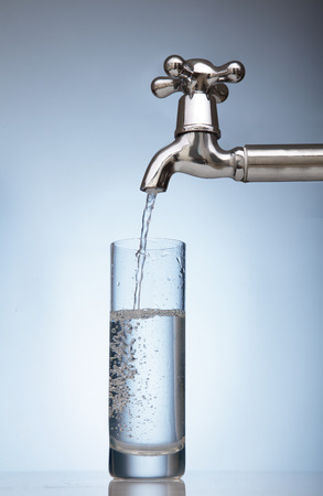 sauberes Wasser wird in ein Glas aus dem Wasserhahn gegossen Standard-Bild
