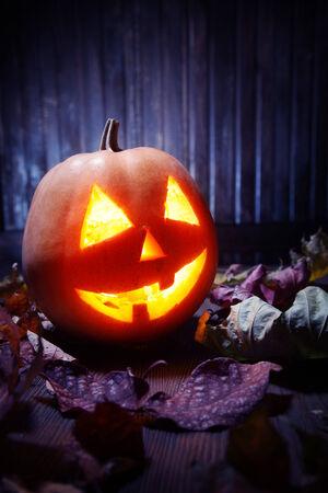 carved pumpkin: Jack o lanterns  Halloween pumpkin face on wooden background and autumn leafs
