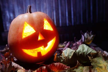 jack o lantern: Jack o lanterns  Halloween pumpkin face on wooden background and autumn leafs