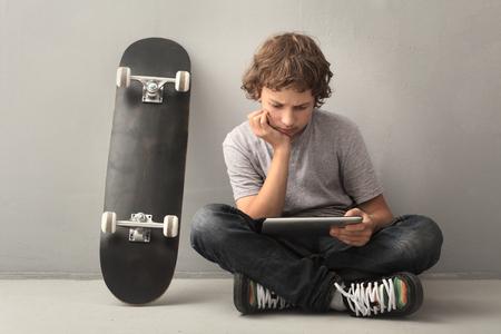 십대는 태블릿 PC와 스케이트 보드에 앉아
