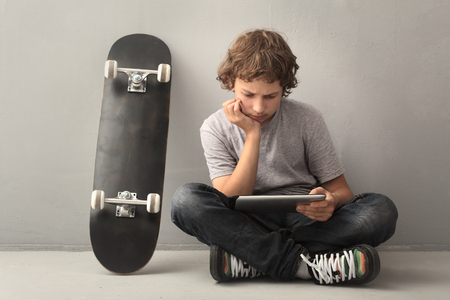 only teenagers: teenager sitting on skateboard with tablet pc