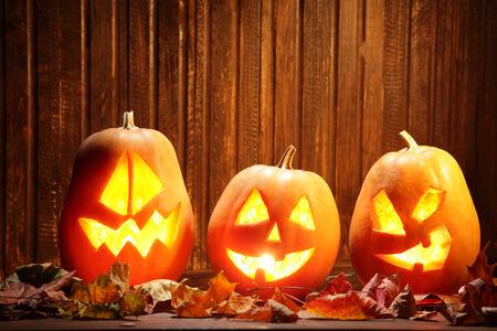lantern: Jack o lanterns  Halloween pumpkin face on wooden background and autumn leafs