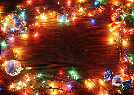 christmas bulbs: Christmas garlands of lamps on a wooden background. Frame of Christmas lights