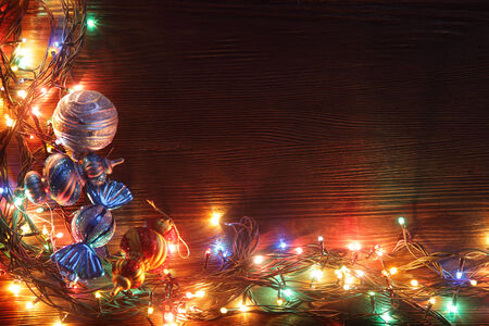 Christmas garlands of lamps on a wooden background. Frame of Christmas lights photo