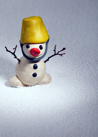 little snowman made of plasticine standing on real snow, Christmas gift-hack photo