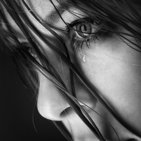 fille triste: pleurer une fille de beauté sur fond noir Banque d'images