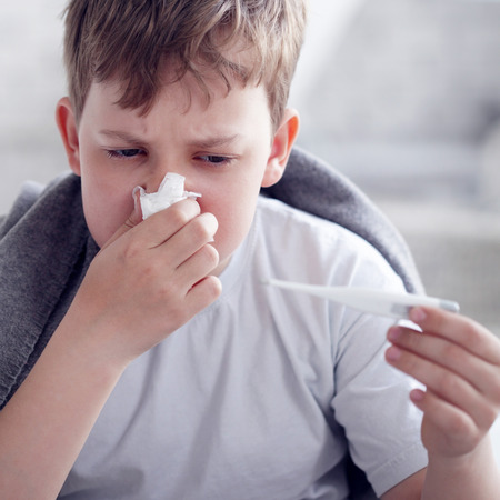 catarrh: teen measures the temperature of the body