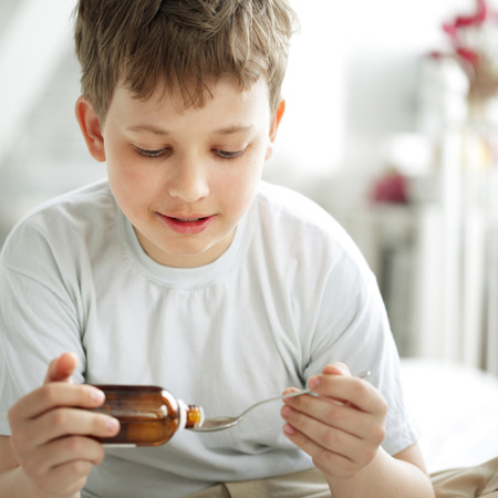 boy drinking cough syrup photo