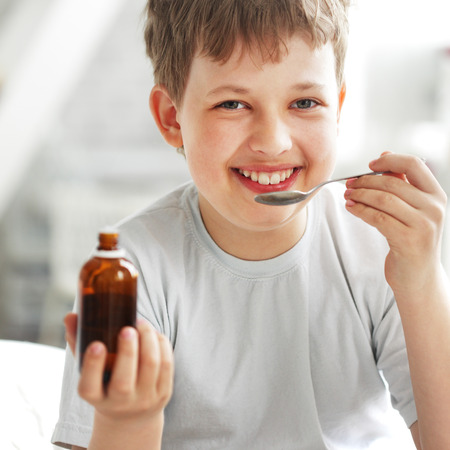 happy boy drinking cough syrup photo