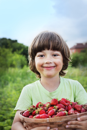 hand basket: cheerful boy with basket of strawberry