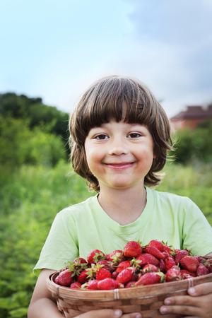 strawberry baskets: cheerful boy with basket of strawberry