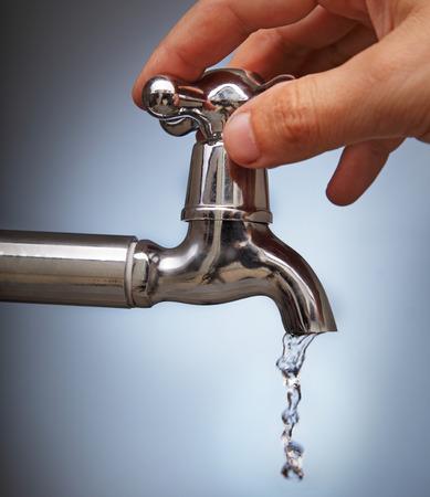 llave agua: la mano del hombre cierra la fuga de agua desde el grifo de metal