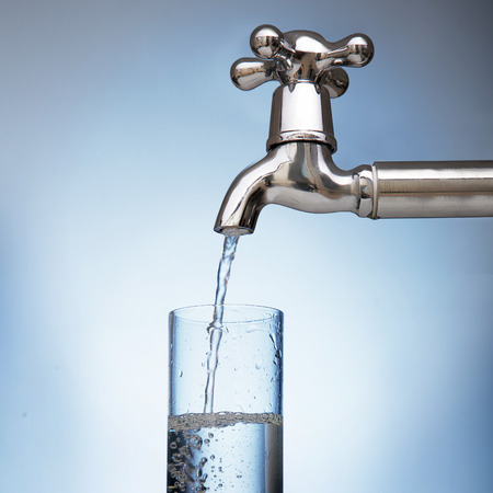 sauberes Wasser wird in ein Glas aus dem Wasserhahn gegossen