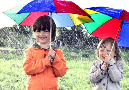 lluvia paraguas: dos hermanos juegan en la lluvia al aire libre