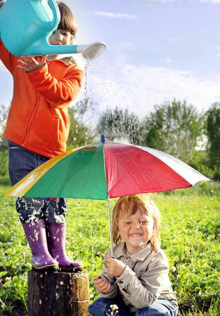 2 persons only: two brothers play in rain outdoors