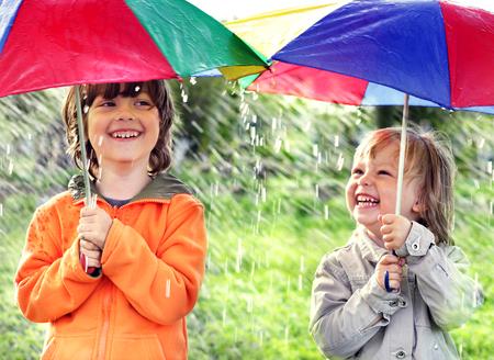 uomo sotto la pioggia: due fratelli felice con ombrello all'aperto