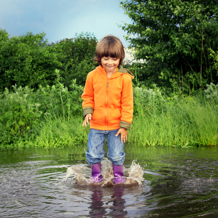 handcarves: happy boy jump in puddle Stock Photo