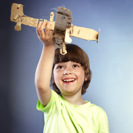 boy playing with a paper airplane photo