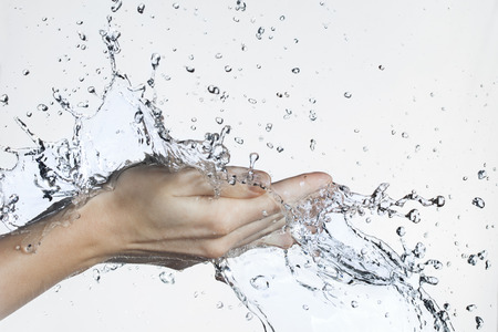 white wash: Splash of Water in Woman Hand Stock Photo