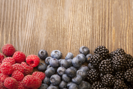 raspberries and blackberry scattered on the wooden table