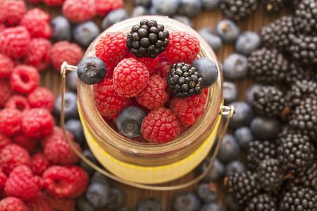 different berries (blueberries raspberries blackberries) in a basket on a wooden table photo
