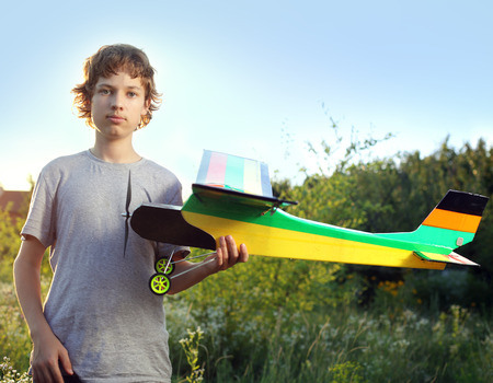 Teen with homemade radio-controlled model aircraft (airplane is hand made not copyright) photo