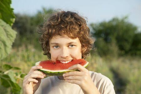 comiendo frutas: adolescente feliz comiendo sandía en el jardín