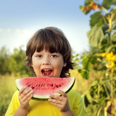 happy child eating watermelon in the garden photo