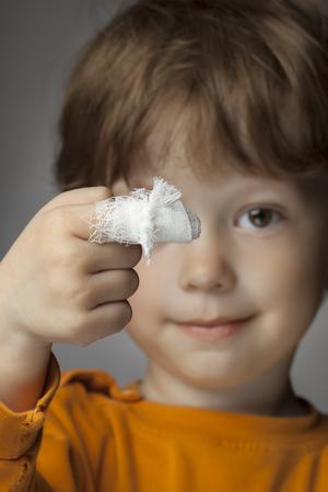 彼の指に包帯傷を持つ少年