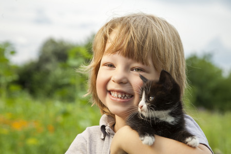 kittens: Happy kid with a kitten in her arms in nature