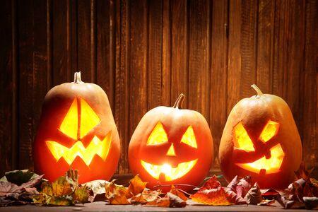 calabazas de halloween: Cara de la calabaza Jack o linternas de Halloween en el fondo y el otoño las hojas de madera