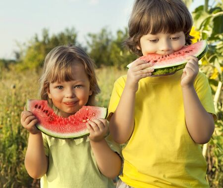 eating in the garden: happy child eating watermelon in the garden Stock Photo