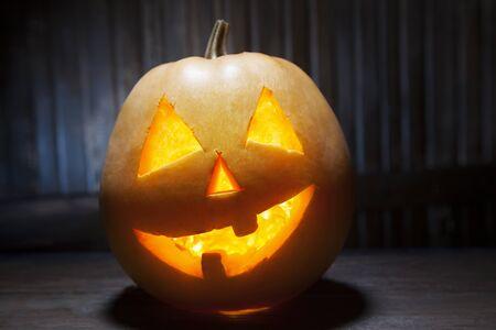 pumpkin face: Jack o lanterns Halloween pumpkin face on wooden background and autumn leafs Stock Photo