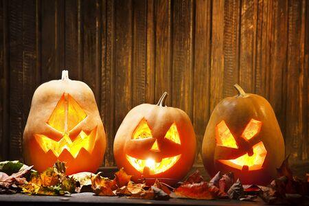 calabazas de halloween: Jack o lanterns Halloween pumpkin face on wooden background and autumn leafs Foto de archivo