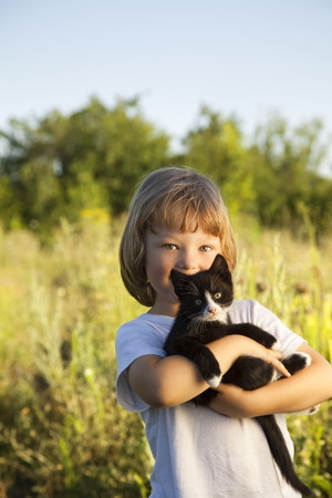 cute kittens: Happy kid with a kitten in her arms in nature