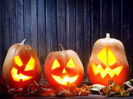 halloween lantern: Jack o lanterns  Halloween pumpkin face on wooden background and autumn leafs