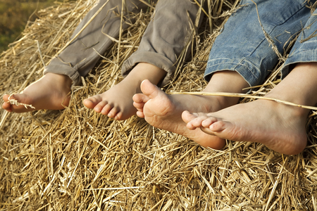Barefoot childrens feet in the hay Stock Photo