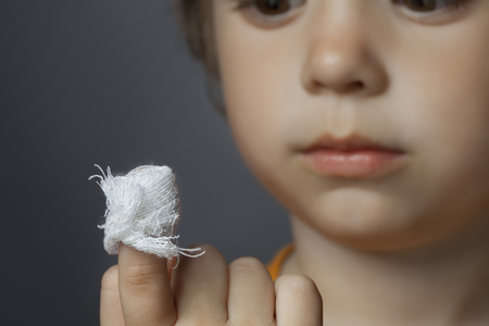 bandaged: boy with a bandaged wound on his finger (focus on finger)
