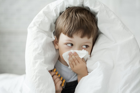 tosiendo: muchacho limpia la nariz con un pañuelo