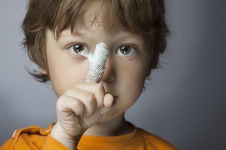 彼の指 (指にフォーカス) に包帯傷を持つ少年