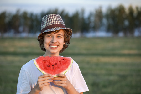 haystack: teenager eating watermelon on a haystack
