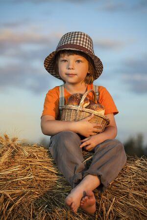 comiendo pan: Muchacho con la cesta de bollos en el fondo de montones de heno en un campo